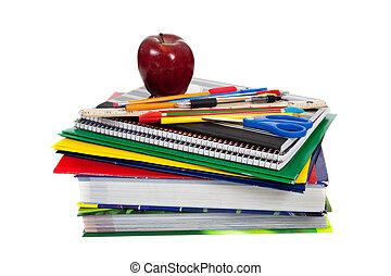 Un montón de libros de texto con suministros escolares encima