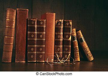 Un montón de libros viejos con gafas en el escritorio