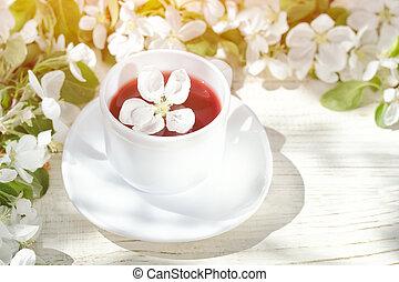 Un montón de té y flores en un fondo blanco de madera. Día soleado