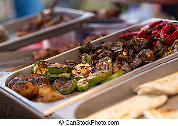 Un mostrador con bandejas de metal que contienen comida a la parrilla. Comida y equipo de cocina en un festival de comida callejera