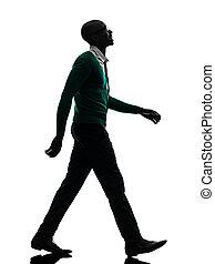 Un negro africano caminando sonriendo en un estudio de silueta en blanco