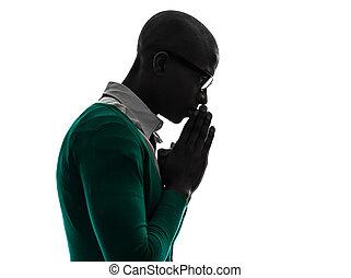 Un negro africano pensando en una silueta de oración pensativa
