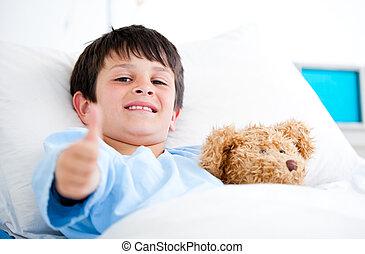 Un niño abrazando a un oso de peluche en la cama del hospital