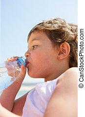 Un niño bebiendo de una botella de agua