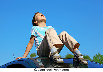 Un niño con los ojos cerrados sentado en el techo del auto en el cielo azul
