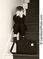 Un niño de la escuela deprimido sentado en las escaleras.
