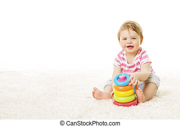 Un niño de un año sentado en una alfombra sobre fondo blanco