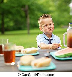 Un niño en la mesa de picnic comiendo comida