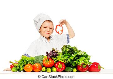 Un niño jugando al chef de cocina preparando ensalada fresca