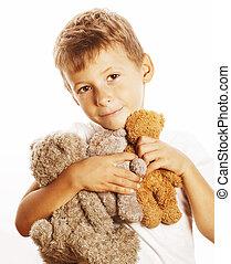 Un niño lindo con muchos osos de peluche abrazados de cerca