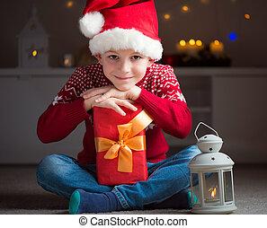 Un niño lindo con sombrero rojo con regalo y esperando a Papá Noel