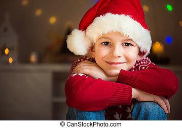 Un niño lindo con sombrero rojo esperando a Santa Claus