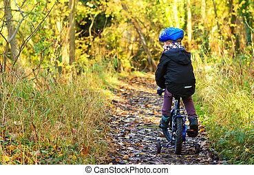Un niño que va en bicicleta por el camino de Woodland