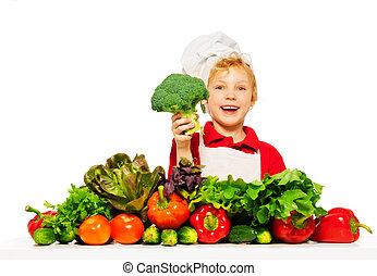 Un niño sonriente con verduras verdes