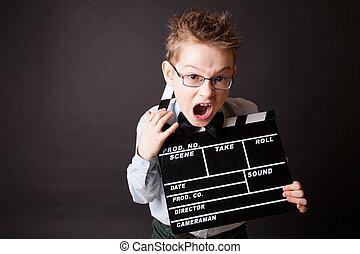 Un niño sosteniendo el tablero de claque en las manos.