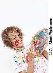 Un niño sucio jugando con pintura