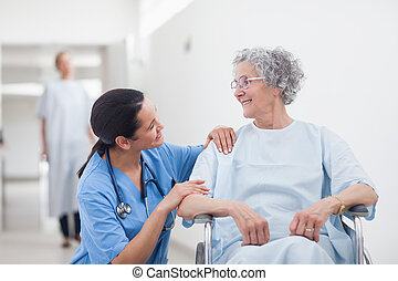 Un paciente mayor mirando a una enfermera