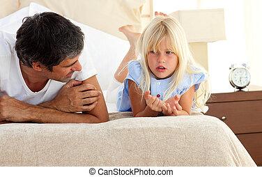 Un padre encantador hablando con su hija en la cama