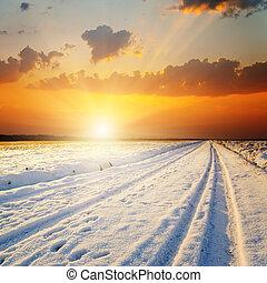 Un paisaje de invierno. Al atardecer sobre la carretera con nieve