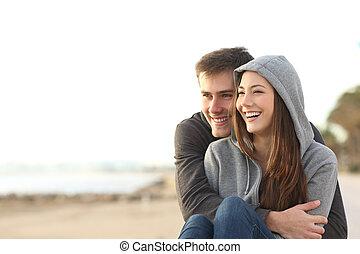 Un par de adolescentes felices mirando hacia la playa