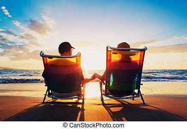 Un par de ancianos sentados en la playa mirando el atardecer
