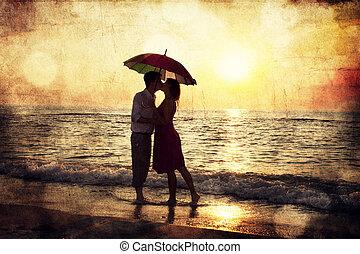 Un par de besos bajo el paraguas en la playa al atardecer. Fotografía a la antigua imagen.