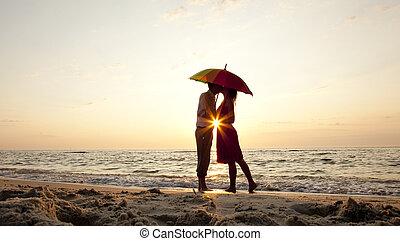 Un par de besos bajo el paraguas en la playa al atardecer.