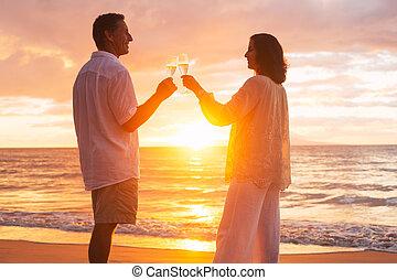 Un par de copas de champán en la playa al atardecer