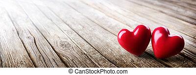Un par de corazones enamorados en una mesa de madera vintage, día de San Valentín
