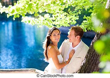 Un par de enamorados abrazados en el lago azul del bosque