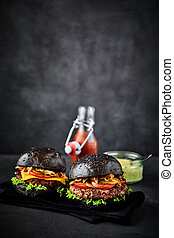 Un par de hamburguesas en servilleta negra con espacio de copia