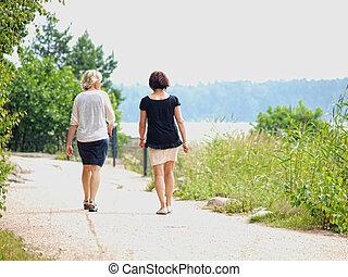 Un par de mujeres caminando mientras hablan en una carretera de gravilla en verano