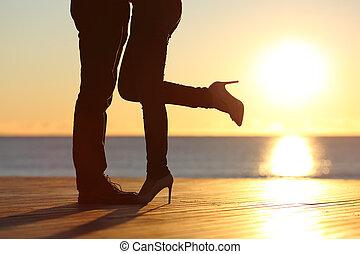 Un par de piernas abrazándose en la playa
