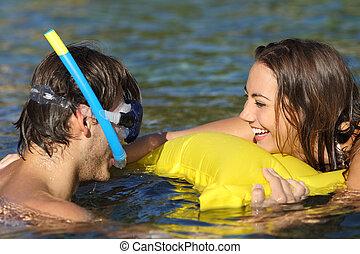 Un par de turistas felices bromeando en la playa
