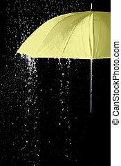 Un paraguas amarillo bajo gotas de lluvia con fondo negro