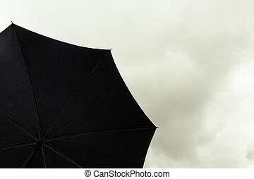 Un paraguas negro en el cielo nublado