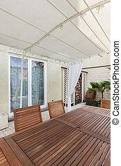 Un patio cubierto con muebles de jardín