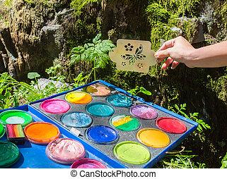 Un pincel artista está pintando una escena de primavera, de la naturaleza del verano en un fondo blanco y aislado. Hay mariposas saliendo de la salpicadura de pintura. Úsalo como concepto creativo o imaginación.