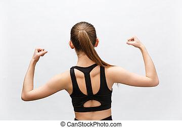 Un plano de mujer deportista levanta la mano para mostrar sus músculos, se siente confiado en la victoria, se ve fuerte e independiente, sonríe positivamente, se para contra el fondo gris. Concepto deportivo