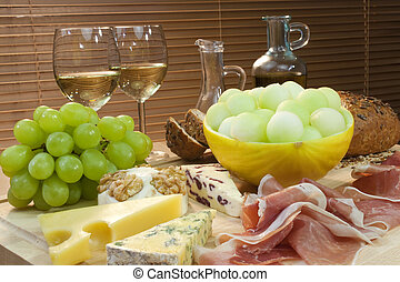 Un plato de comida mediterránea incluyendo queso, uvas, vino blanco, pan, jamón de Parma, melón, aceite de oliva y vinagre bálsamo. Un disparo en una hermosa luz caliente.