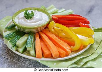 Un plato de verduras con salsa