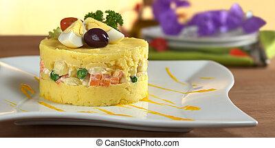 Un plato peruano tradicional llamado causa de puré de papas amarillas y blancas mezcladas con aji y jugo de lima y lleno de verduras (corno, guisantes, zanahorias) y mayonesa y guarnición