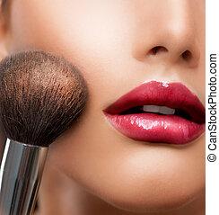 Un primer plano de maquillaje. Cepillo cosmético. La piel perfecta