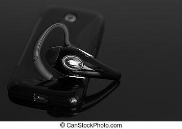 Un primer plano de un bluetooth sin manos cerca del teléfono móvil.