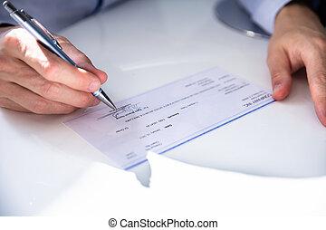 Un primer plano de un cheque de relleno a mano