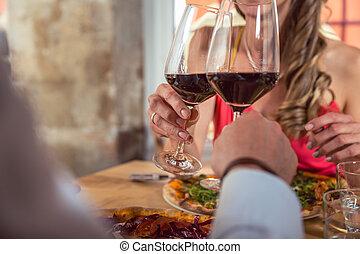 Un primer plano de una pareja brindando con copas de vino