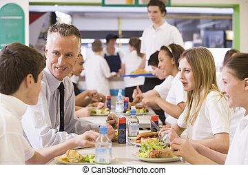 Un profesor comiendo con sus estudiantes en la cafetería de la escuela