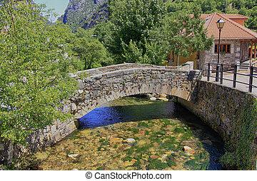 Un puente de piedra sobre un arroyo