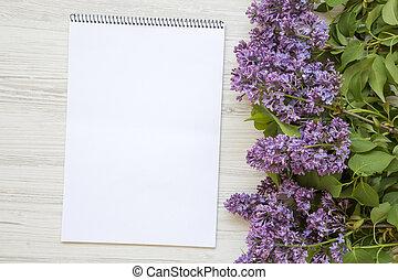 Un ramo de flores lilas con cuaderno en un fondo blanco de madera. Día de las madres. Copia espacio. Desde arriba, plano.