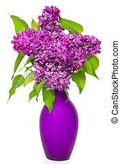 Un ramo de flores lilas en florero